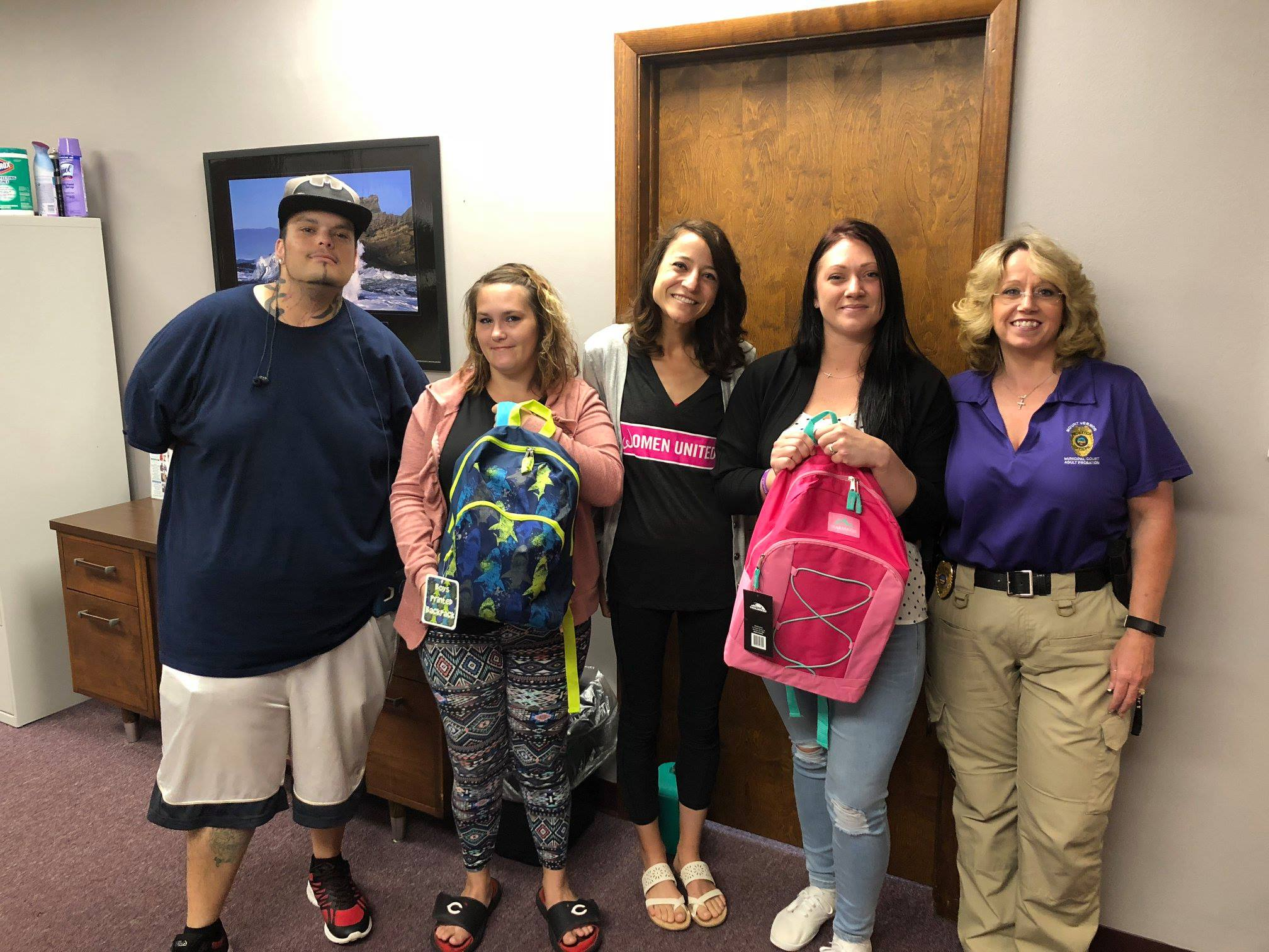 Elizabeth Doolittle, Program Director, is pictured with parents of book bag recipients at the Mount Vernon Municipal Court Probation Dept.. Also shown is Laura and her two children who very excited about receiving their book bags.